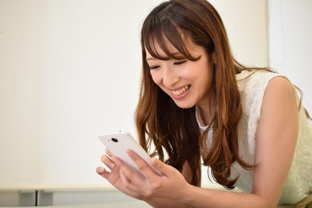 スマホアプリをいじる女性